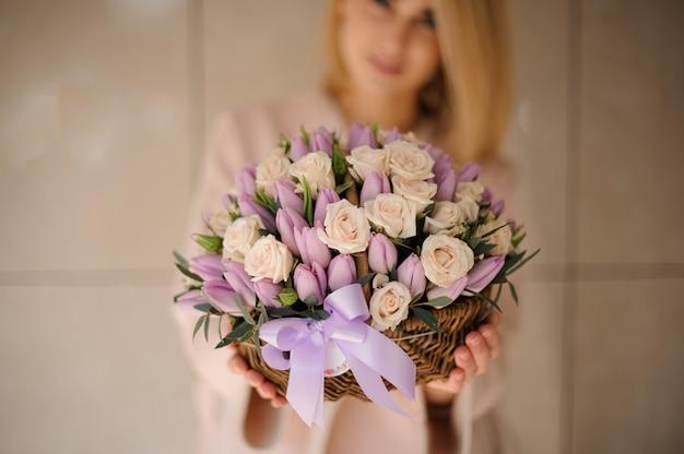 Roses et tulipes dans le panier dans les mains de la fille Photo Premium