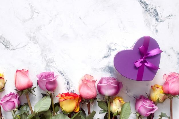 Roses violettes et jaunes, boîte présente sur fond blanc Photo Premium