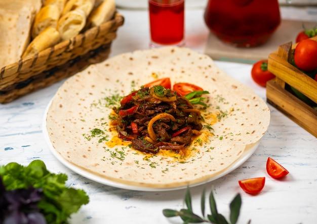 Rôti de viande et de légumes aux herbes sur une assiette blanche avec du pain, des légumes et un verre de vin Photo gratuit
