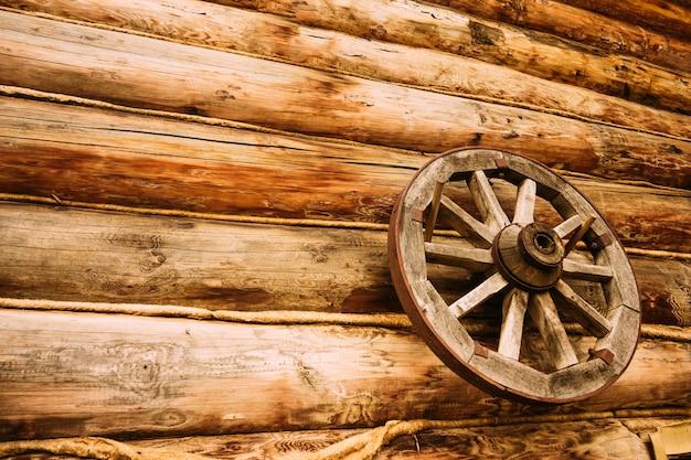 Roue en bois sur le mur de la maison en rondins Photo Premium