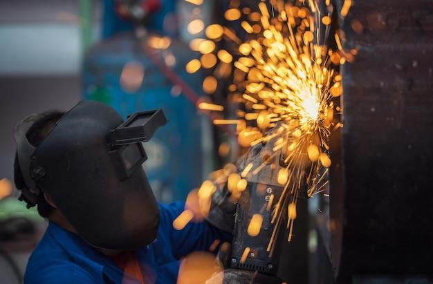 Roue électrique meulage sur structure d'acier en usine Photo Premium