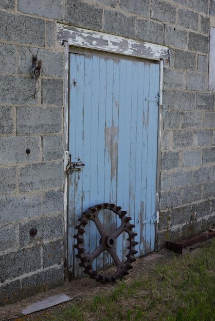 Roue de garniture en acier vintage devant une porte de grange antique bleue en saskatchewan, canada Photo Premium