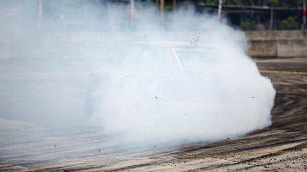 La roue de voiture tourne et crée des cascades de fumée, drag racing sur une piste de course rapide, Photo Premium