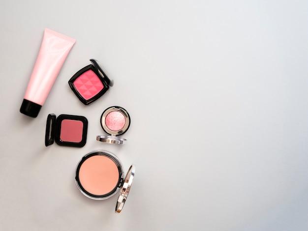 Rouge à lèvres, outils, eye-liner, blush, parfum, ombre à paupières et poudre cosmétique à thème bleu se maquillent sur le cadre pour la promotion. ensemble de produits cosmétiques décoratifs. espace de copie. Photo Premium