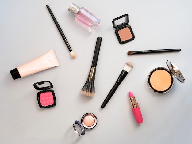 Rouge à lèvres, outils, eye-liner, blush, parfum, ombre à paupières et poudre cosmétique à thème bleu se maquillent sur le cadre pour la promotion. ensemble de produits cosmétiques décoratifs. kit de vente Photo Premium
