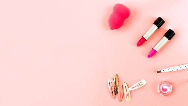 Rouges à lèvres et éponge près des épingles à cheveux Photo gratuit