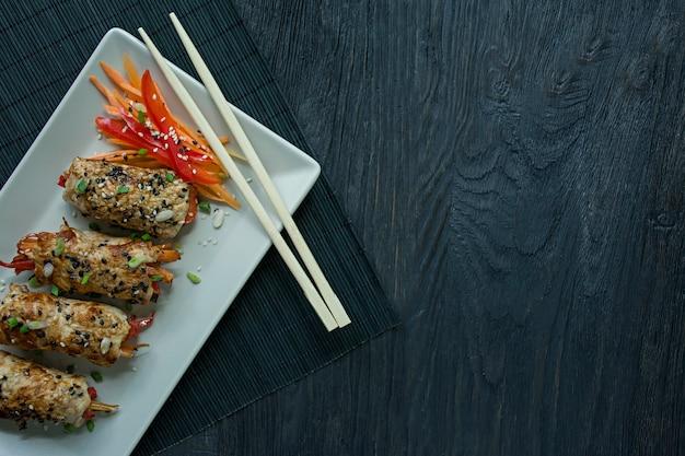 Roulades de poitrine de poulet faites maison avec des légumes verts, des tranches de carotte et du poivron sur une assiette rectangulaire légère. Photo Premium