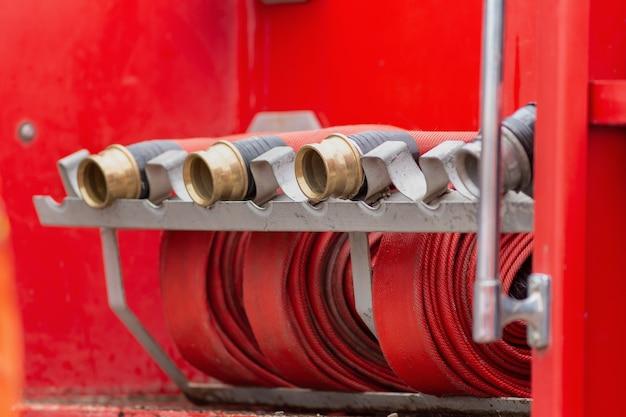 Roulé dans un tuyau d'incendie rouge, extincteurs d'équipement d'incendie prêts à l'emploi Photo Premium