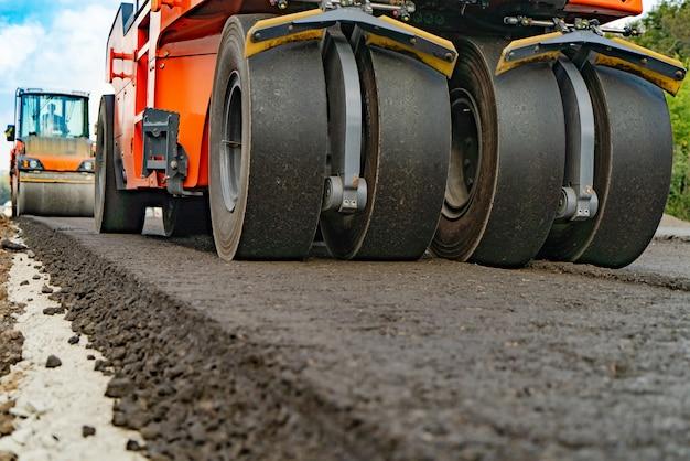 Rouleau d'asphalte qui empile et presse l'asphalte chaud tout en faisant une nouvelle route. Photo Premium