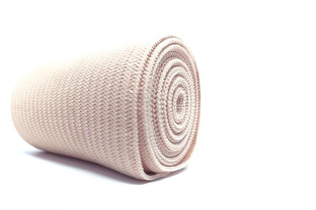 Rouleau de bandage élastique médical pour kit de premiers soins isolé sur blanc. Photo Premium
