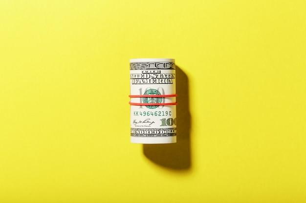 Un Rouleau De Billets De Cent Dollars Américains Est Attaché Avec Une Bande élastique Rouge Sur Fond Jaune. Photo Premium