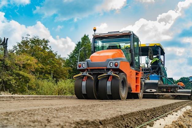 Rouleau, équipement de construction, sur le site de réparation de la route. Photo Premium