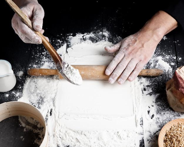 Rouleau à pâtisserie en bois dans les mains des hommes Photo Premium