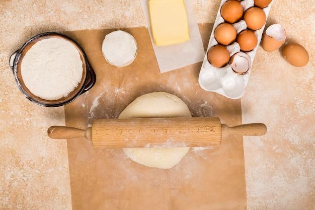 Rouleau à pâtisserie sur une boule de pâte avec des ingrédients sur un comptoir en bois Photo gratuit