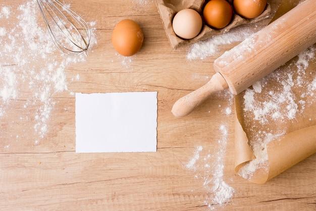 Rouleau à pâtisserie avec oeufs en rack, papier et farine Photo gratuit