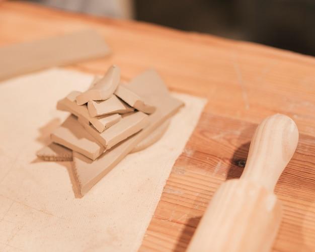 Un rouleau à pâtisserie et une pile d'argile humide de différentes formes sur un bureau en bois Photo gratuit