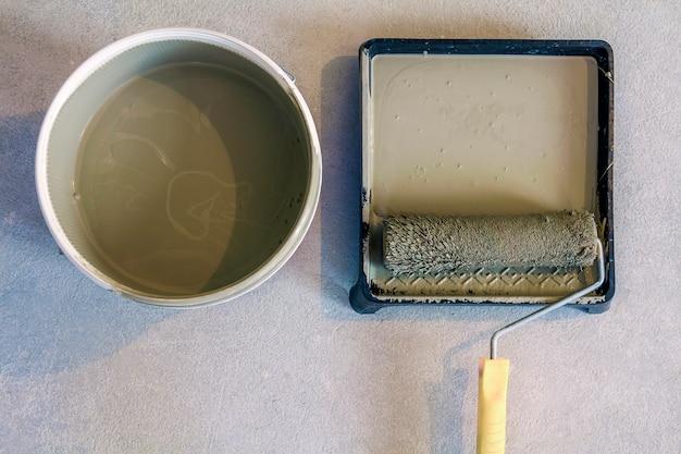 Rouleau à peinture dans le bac avec peinture peut sur le sol en béton. Photo Premium