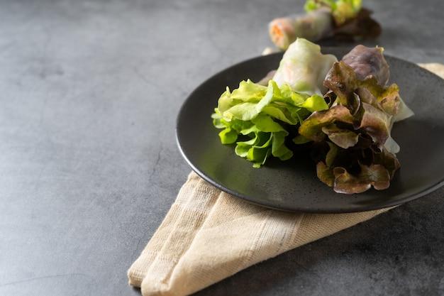 Rouleau de printemps de légumes frais, aliments propres, salade pour perdre du poids, sur fond sombre Photo Premium