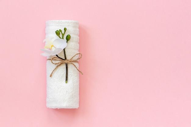 Rouleau de serviettes blanc attaché avec une corde avec un brin de fleur d'orchidée sur du papier rose. Photo Premium