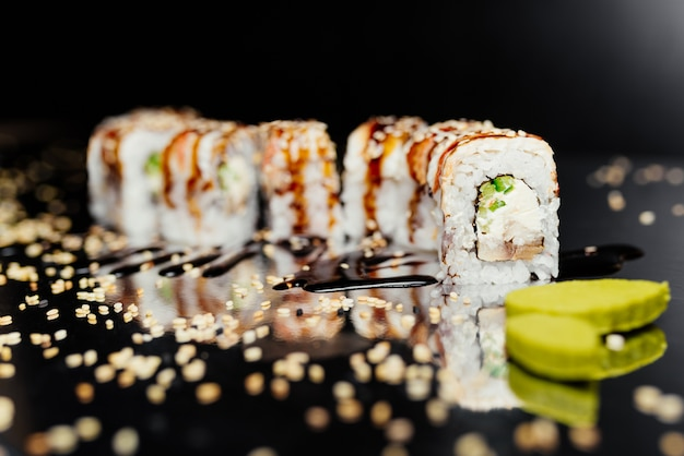 Rouleau de sushi dragon d'or fait de nori, riz mariné, fromage, concombre, unangile Photo gratuit