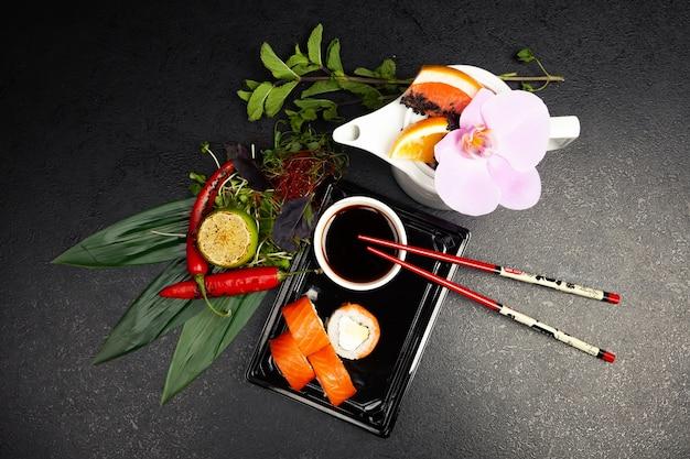 Rouleau De Sushi Philadelphie à L'avocat Décoré D'herbes Sur Une Assiette, Sushi Japonais Classique. Cuisine Japonaise Traditionnelle Avec Maki. Photo Premium