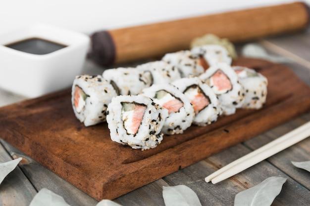 Rouleau de sushi sur un plateau en bois avec sauce soja et baguettes Photo gratuit