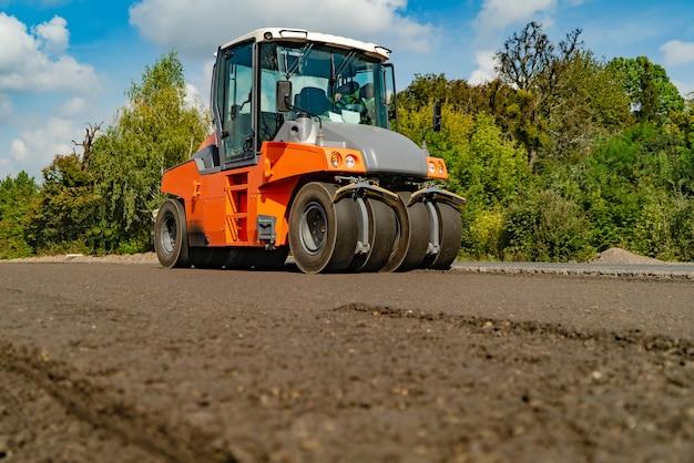 Rouleau travaillant sur le nouveau chantier de construction de la route Photo Premium