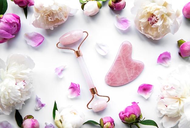 Rouleau De Visage En Jade Pour La Thérapie De Massage Du Visage De Beauté Et Les Pivoines Roses. Mise à Plat Sur Fond Blanc Photo Premium