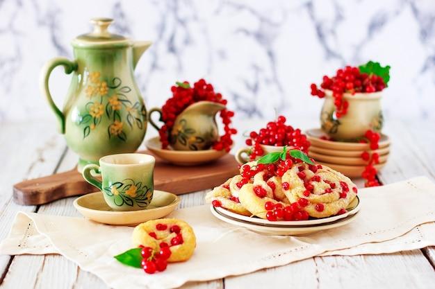 Rouleaux de biscuits au fromage cottage aux groseilles rouges sur une plaque en céramique avec service à café ou à thé en céramique vintage, heure du thé, petit-déjeuner, bonbons d'été Photo gratuit