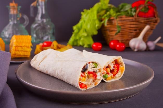 Rouleaux de burrito aux légumes sur un tableau noir et légumes, tomates cerises et ail à l'arrière-plan Photo Premium