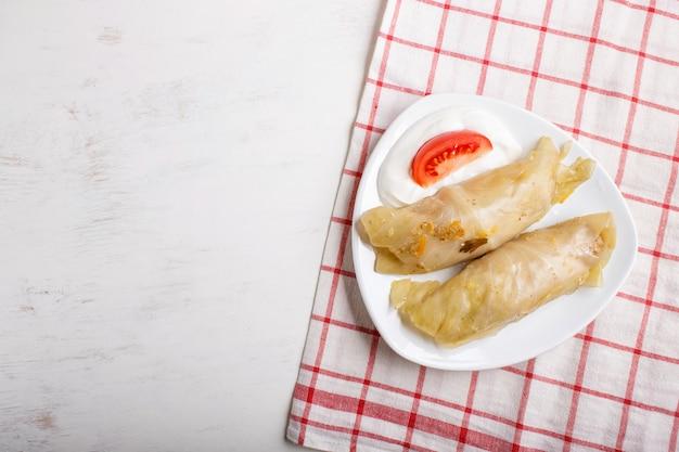 Rouleaux de chou au bœuf, riz et légumes sur une nappe en lin sur un fond en bois blanc. Photo Premium