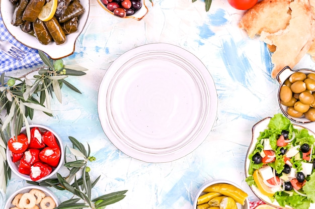 Rouleaux de chou turc et diverses collations de la cuisine nationale. riz dans les feuilles de vigne et les olives. nourriture pour un déjeuner oriental traditionnel. espace libre pour le texte, assiette vide Photo Premium