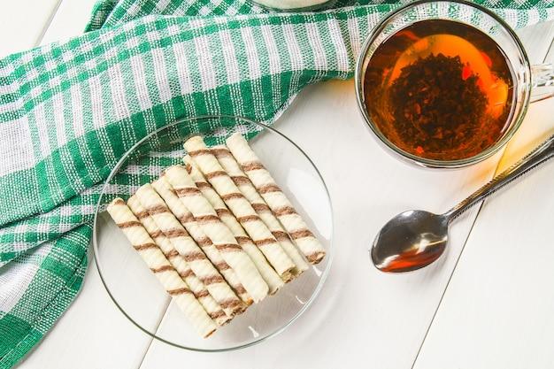 Rouleaux de gaufrettes à rayures, délicieux casse-croûte au chocolat sur une table en bois blanc. Photo Premium