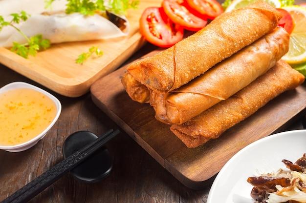 Rouleaux de printemps frits croustillants avec sauce aux prunes et salade, tranches de citron sur la table en bois Photo Premium