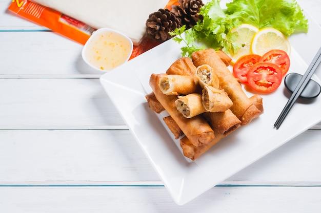 Rouleaux de printemps frits croustillants avec sauce aux prunes et salade, tranches de citron Photo Premium