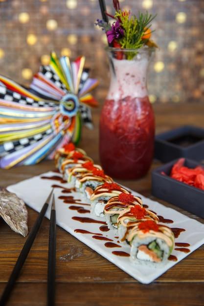 Rouleaux de sushi au saumon et concombre recouverts d'avocat Photo gratuit