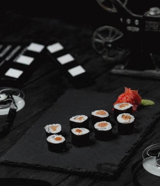 Rouleaux de sushi au saumon fumé sur tableau noir. Photo gratuit