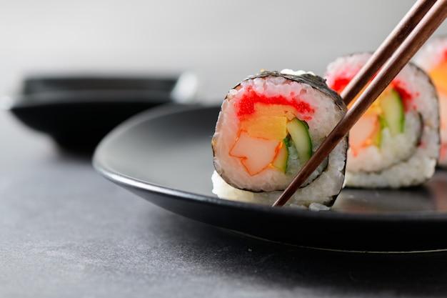 Rouleaux De Sushi (bâtonnets De Légumes, D'inari Et De Crabe) Avec Des Baguettes Photo Premium
