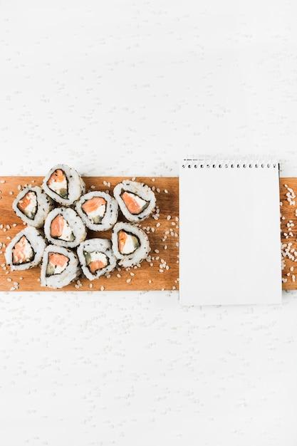 Rouleaux de sushi et bloc-notes en spirale sur un plateau en bois avec éclaboussures de riz non cuit sur fond blanc Photo gratuit