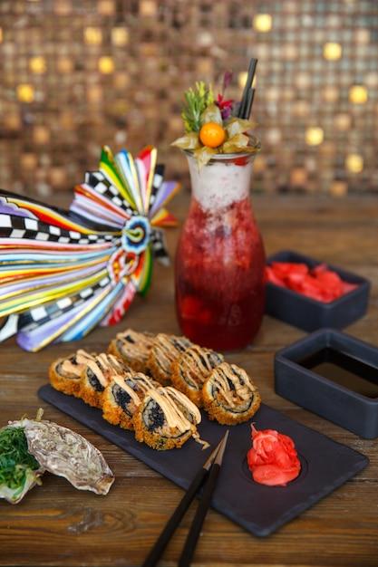Rouleaux de sushi chauds au gingembre et au wasabi sur un plateau en pierre noire Photo gratuit