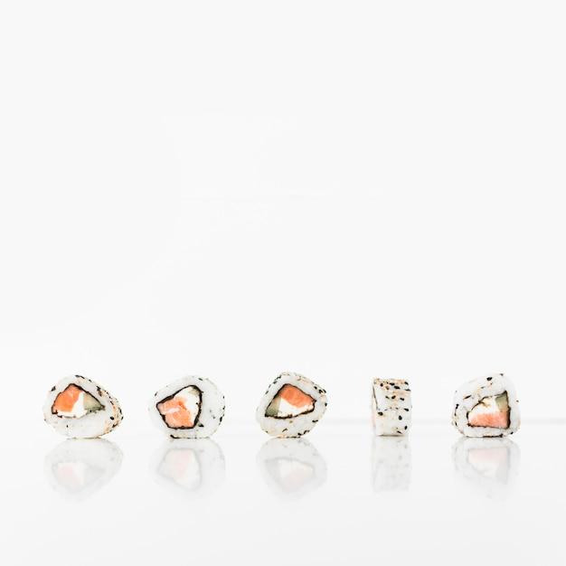 Rouleaux de sushi sur fond réfléchissant blanc Photo gratuit
