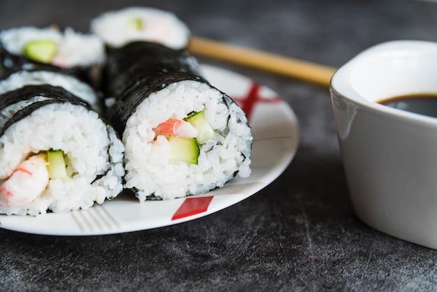 Rouleaux de sushi, sauce soja et baguettes Photo gratuit