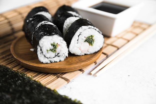 Rouleaux de sushi et sauce soja sur une natte de bambou Photo gratuit