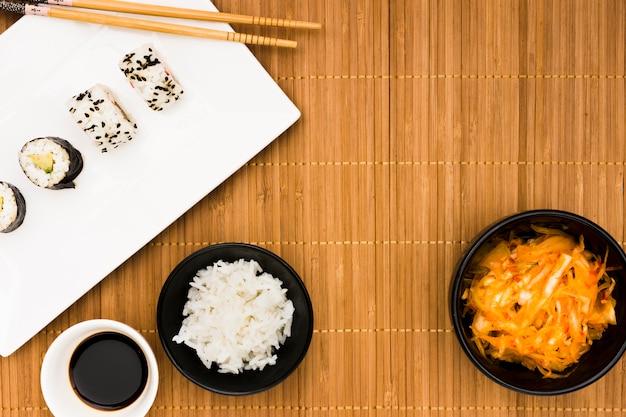 Rouleaux de sushi; sauce soya; riz cuit à la vapeur et salade sur napperon Photo gratuit