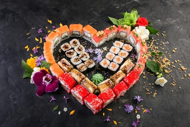 Rouleaux et sushis sur un fond noir d'ardoise, cuisine japonaise Photo Premium