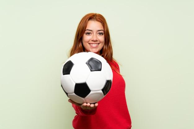 Rousse adolescente avec pull sur vert isolé, tenant un ballon de foot Photo Premium