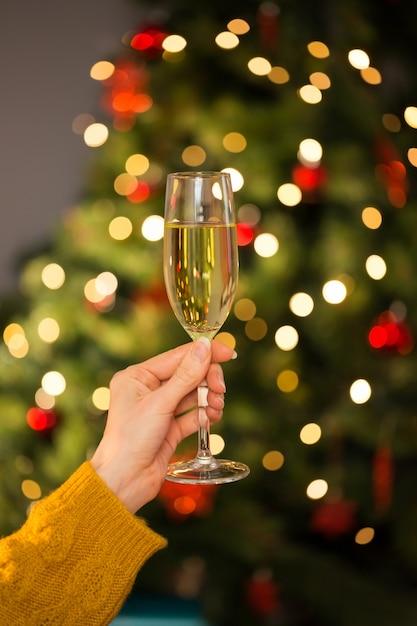 Rousse tenant un verre de champagne sur un canapé à noël Photo Premium