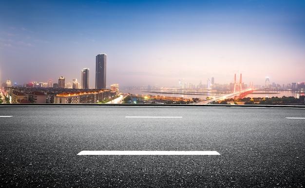 Route d'asphalte vide et skyline moderne dans la nuit Photo Premium