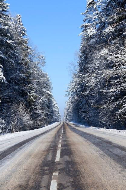 Route Asphaltée Avec Des Marques Blanches Sous La Neige, Une Partie Des Ornières De Neige Des Voitures Passées A Fondu, Paysage D'hiver Photo Premium