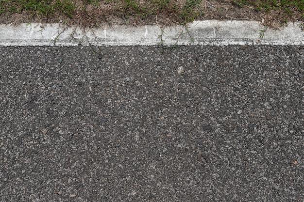 Route asphaltée avec des rayures et de la texture de l'herbe verte fond, espace de copie vide. Photo Premium